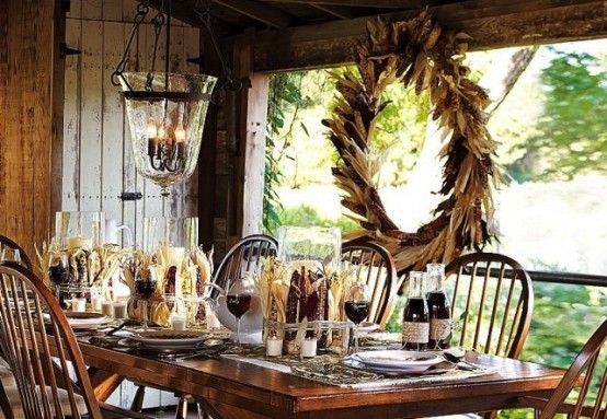 thankgiving-tablescapes; a rustic outdoor setting on  covered patio. A large wreath hangs as decoration and corn has been used as centerpieces