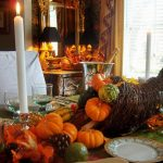 thanksgiving-tablescapes: a rustic cornucopia filled with mini pumpkins, white candles and green glasses