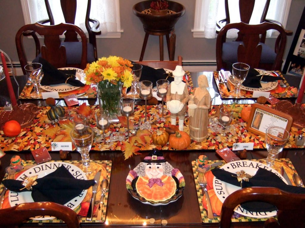 thanksgiving-tablescapes; a bright tavble runner scattered with leaves and mini pumpkins, a vase with orange and yellow flowers, and fun thanksgiving plates