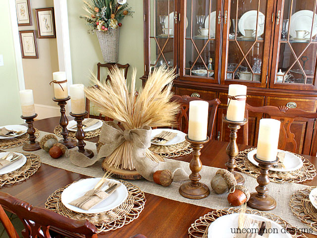 thanksgivingtablescapes: white china plates wheat grass tied with burlap for centerpiece and cream colored candles. acorns are scattered on the table runner