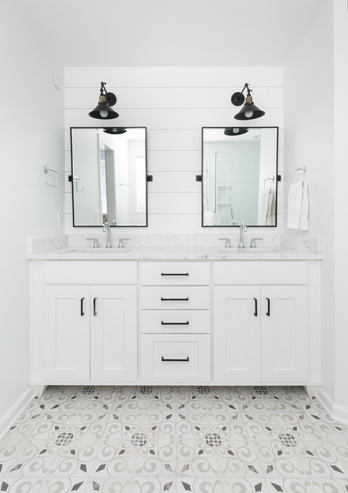 Modern Farmhouse Bathroom Decorating Ideas with White Shiplap Accent Wall that Adorns Black Adjustable Wall Sconces and Double Mirrors Trimmed in Black, White Double Vanity with Black Hardware Pulls, and Decorative White and Gray Tile That Pulls the Look Together
