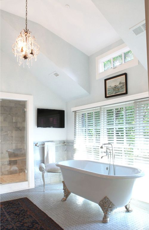 Modern Farmhouse Bathroom Decorating Ideas with Vaulted Ceiling, Large Windows for Plenty of Natural Light, Elegant Chandelier, Freestanding Clawfoot Tub with Decorative Silver Legs, and a Walk-in Shower with Glass Door