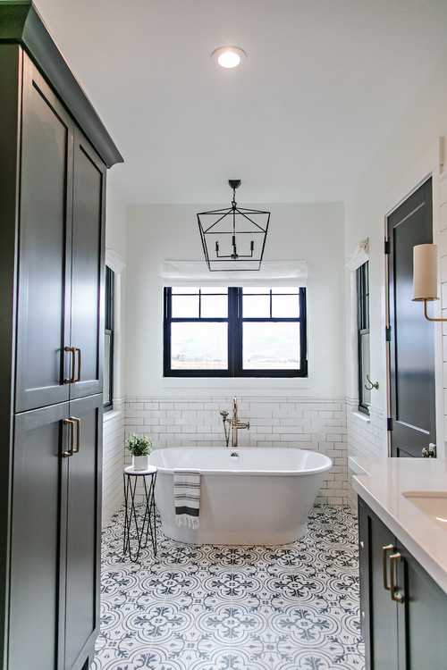 Modern Farmhouse Bathroom Decorating Ideas with a Black Metal Chandelier, Black Trimmed Window, White Walls, Subway Tile Half-Wall, Black Cabinetry, and Black and White Patterned Floor Tile