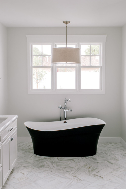 White Modern Farmhouse Bathroom with Curved Black Freestanding Tub and Distressed White and Gray Flooring