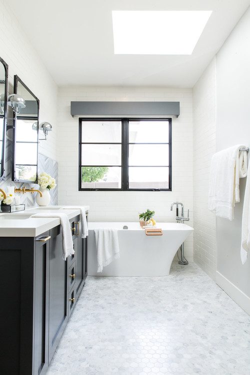 Modern Farmhouse Bathroom Decorating Ideas with a Skylight, White Tiled Walls, Black Trimmed Window, White Freestanding Tub, Black Vanity with Black Trimmed Mirrors, Mixed Metals, and Light Gray Hex Tile Flooring