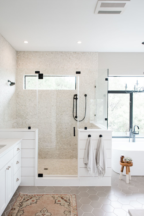 Modern Farmhouse Bathroom Decorating Ideas with White Shiplap and Glass Surround Shower, a Window for Natural Light, Cream Colored Pebble Tile, and All Black Hardware