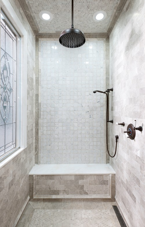 Modern Farmhouse Bathroom Decorating Ideas Feature a Shower with Bronze Fixtures, a Mix of Stone Tiles, a Stained Glass Window, Recessed Lighting, and Convenient Seating