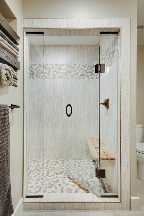 Modern Farmhouse Bathroom Decorating Ideas Features a Shower with Wood Grain Textured Tile, Pebble Tile Flooring and Accent, Bronze Hardware, a Glass Door, and a Teak Seat for a Zen-like Feel