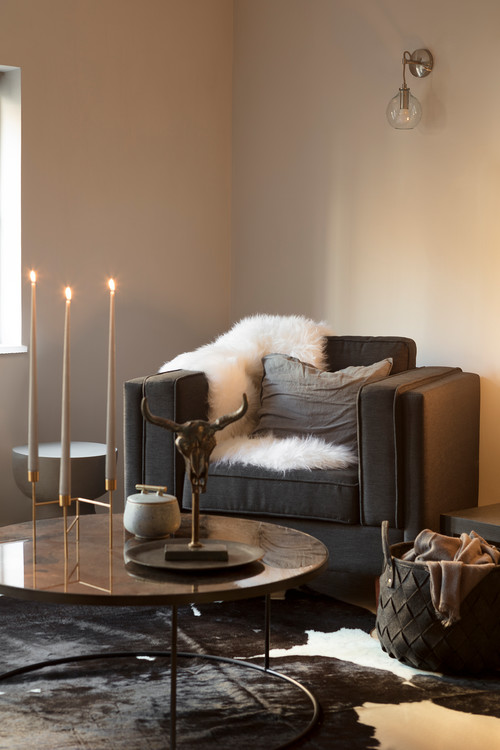 Cozy Scandinavian Living Room with Cowhide Rug and Dark Gray Chair with White Faux Fur Throw