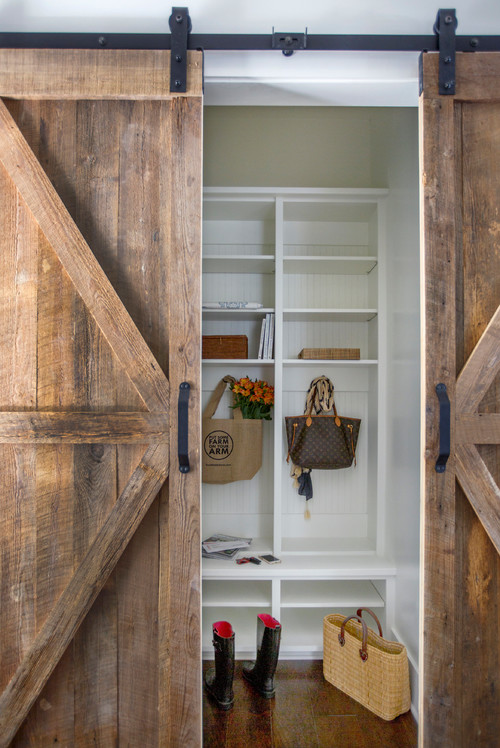 Modern Farmhouse Mudroom Behind Wooden Sliding Barn Doors #modernfarmhouse