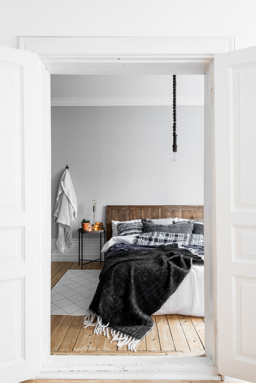 Modern Scandinavian Farmhouse Style Bedroom with Wood Headboard, Black and White Plaid Blanket, Assorted Gray Throw Pillows and Black Throw with White Tassels