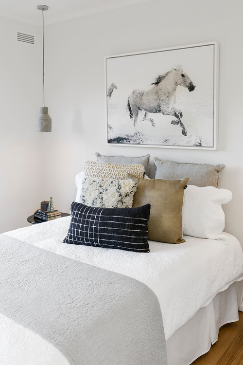 Modern Scandinavian Farmhouse Style Bedroom with Quilted Bedding, Plenty of Pillows and Horse Artwork