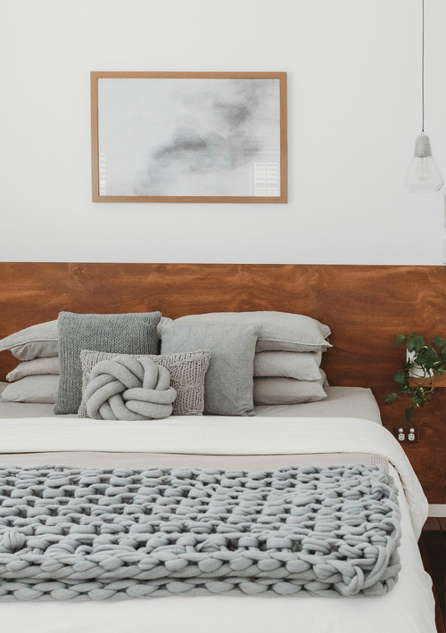 Modern Scandinavian Farmhouse Style Bedroom with Gray Chunky Blanket and Assorted Gray Pillows