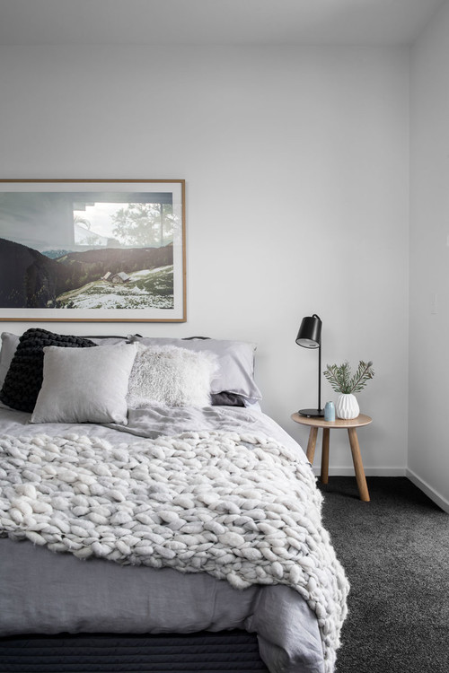 Modern Scandinavian Farmhouse Style Bedroom with Soft Gray Chunky Blanket and Throw Pillows