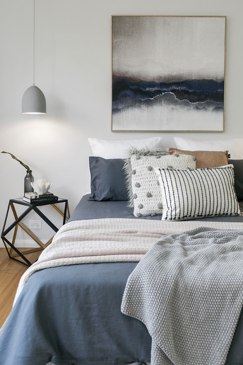 Modern Scandinavian Farmhouse Style Bedroom with Grayish Blue Bedding, Knit Throws, and Pillows and Artwork That Tie The Look Together