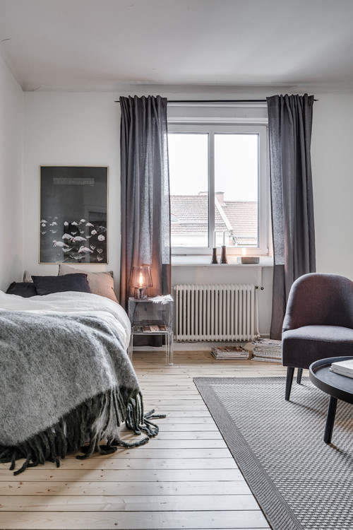 Modern Scandinavian Farmhouse Style Bedroom with Gray Decor and Gray Wool Blanket with Black Tassels