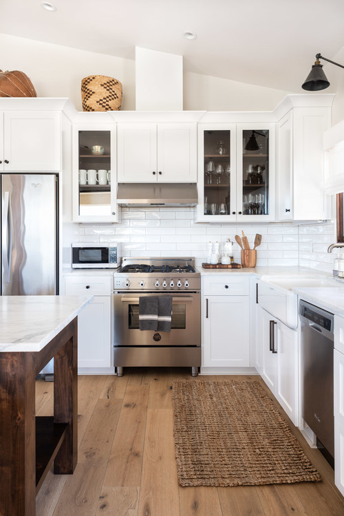White and Wood Modern Farmhouse Kitchen with White Cabinets, Wood Island and Hardwood Floors
