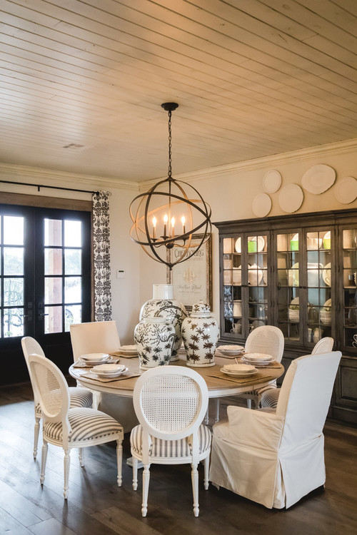 Modern Farmhouse Dining Room with Round Wooden Table and Round Cain Back Dining Chairs