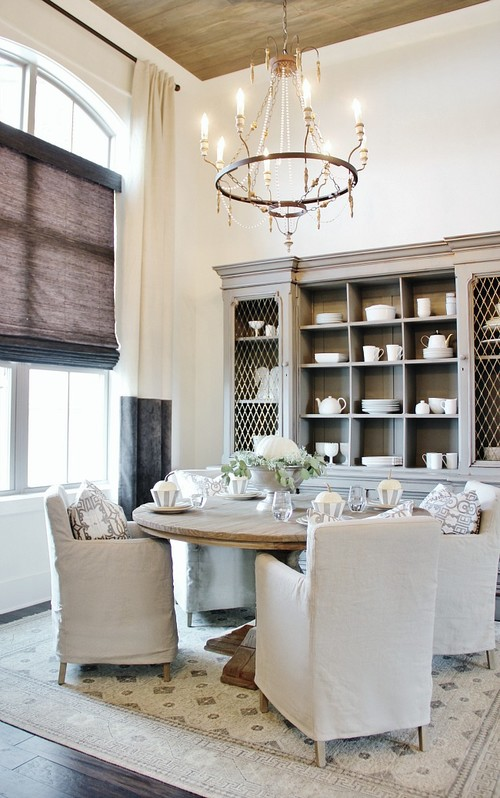 Modern Farmhouse Dining Room with Round Wooden Table and Slipcovered Dining Chairs