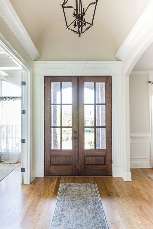Modern Farmhouse Entryway with Wood and Glass French Doors Surrounded by Decorative Trim Work