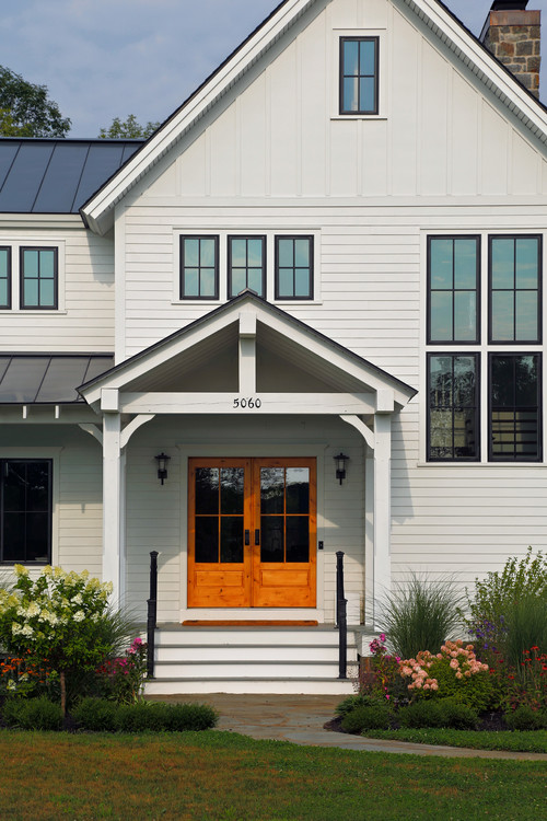 Modern White Farmhouse Exterior with Knotty Alder Wood Front Doors