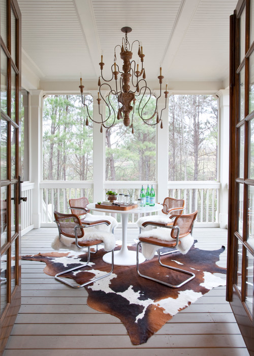 Farmhouse Style Porch with Dining Table and Cowhide Rug