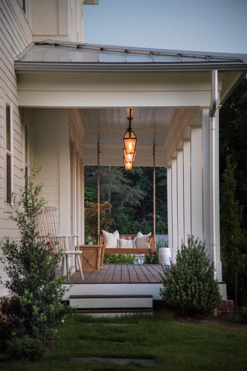 Farmhouse Style Porch with Elegant Lighting and Rope Swing