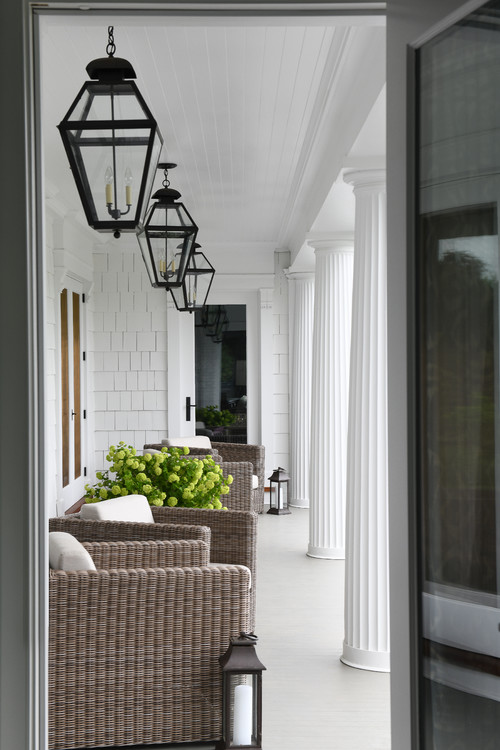 Farmhouse Style Porch with Wicker Chairs and Hanging Lanterns