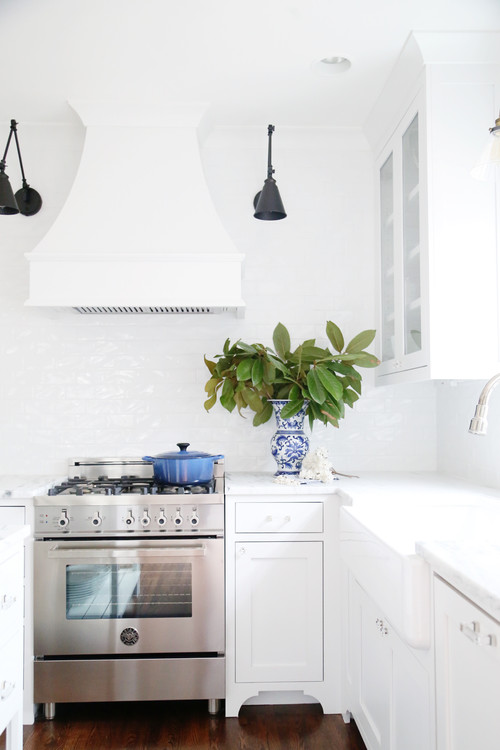 Modern Farmhouse White Kitchen with Black Sconces Above Stove