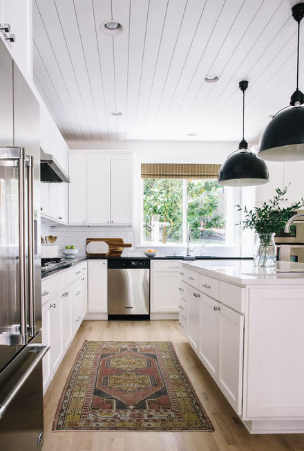 Modern Farmhouse White Kitchen with Black Counters and Black Pendant Lights