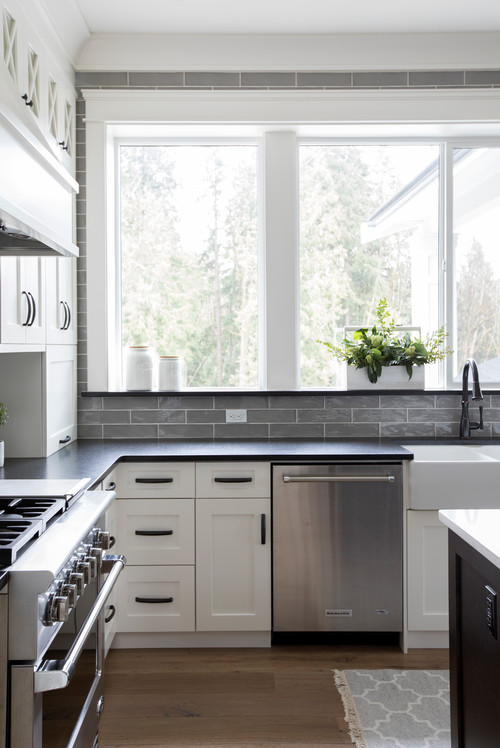 Modern Farmhouse White Kitchen with Black Countertops and Gray Subway Tile Backsplash