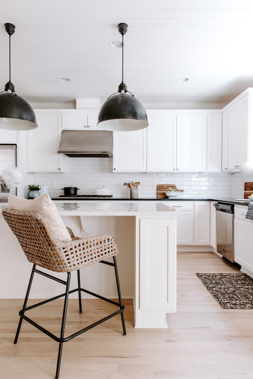 Modern Farmhouse White Kitchen with Black Pendant Lights and Black and Wicker Bar Stool
