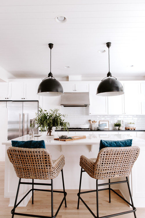 Modern Farmhouse White Kitchen with Black Pendant Lights and Black and Wicker Bar Stools