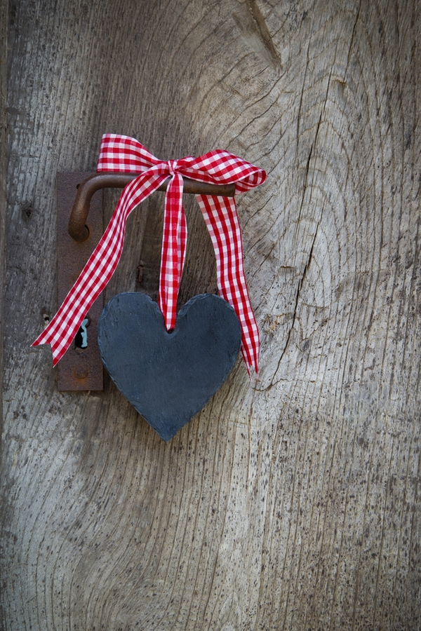 Sometimes it can be hard to find cute farmhouse Valentine's Day decor, but you're in luck. This cute wooden heart on ribbon can go on doorknobs and will look adorable.