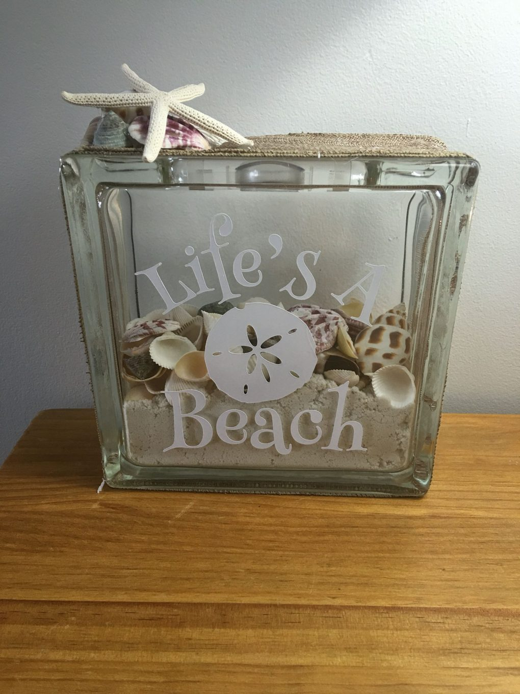 Glass block crafts-Home decor block with a beach theme. Sand and seashells are inside the block and viny lettering reading Life's a beach on the outside of the block.