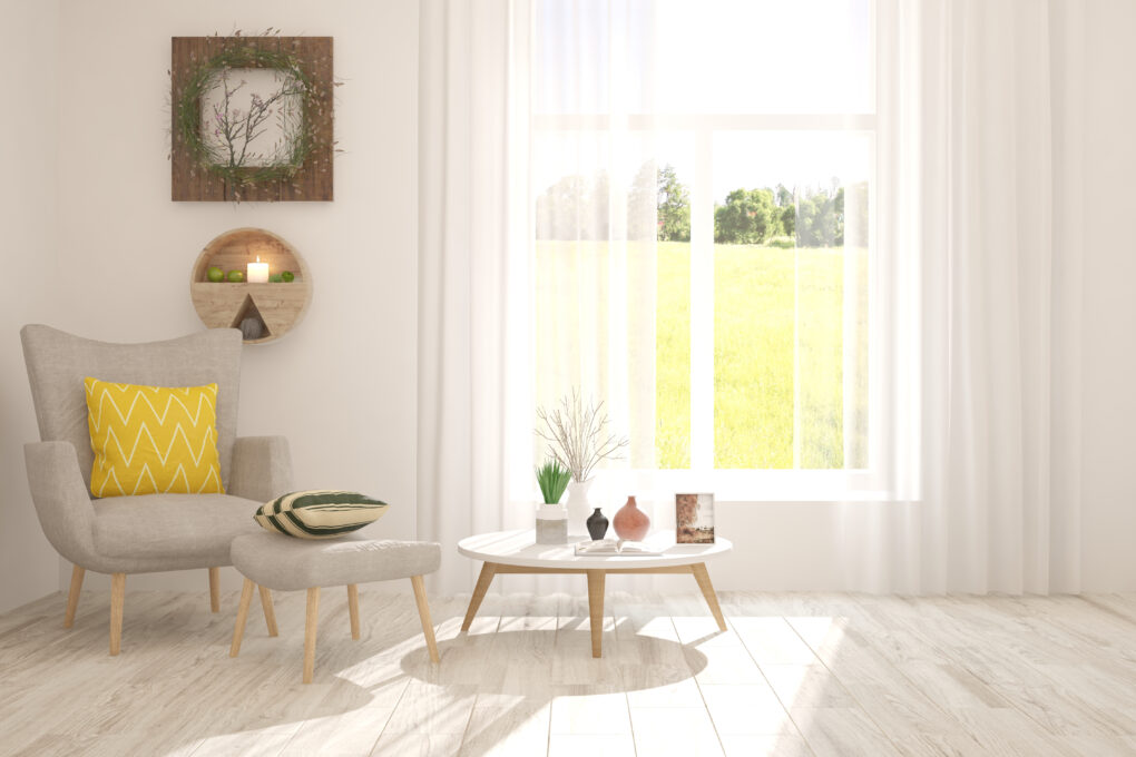 A farmhouse living room with a chair, table, and white curtains.