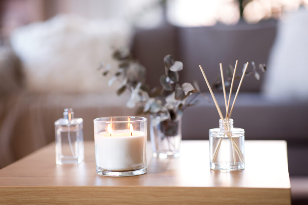 A candle burning on a coffee table next to a reed diffuser.
