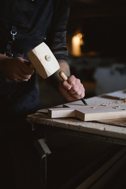 man using a mallet to carve wood
