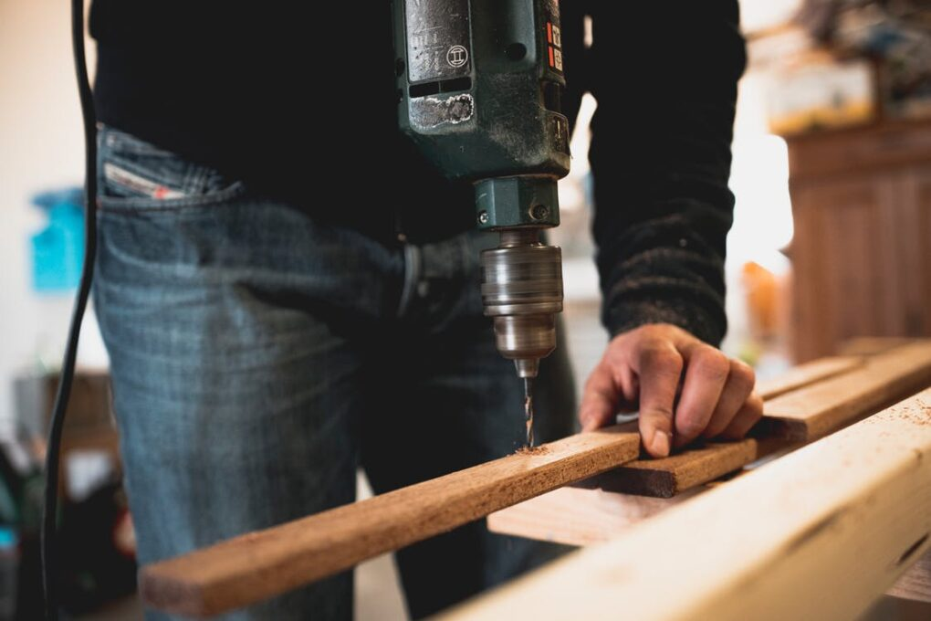 A man holding wooden plank while drilling a hole